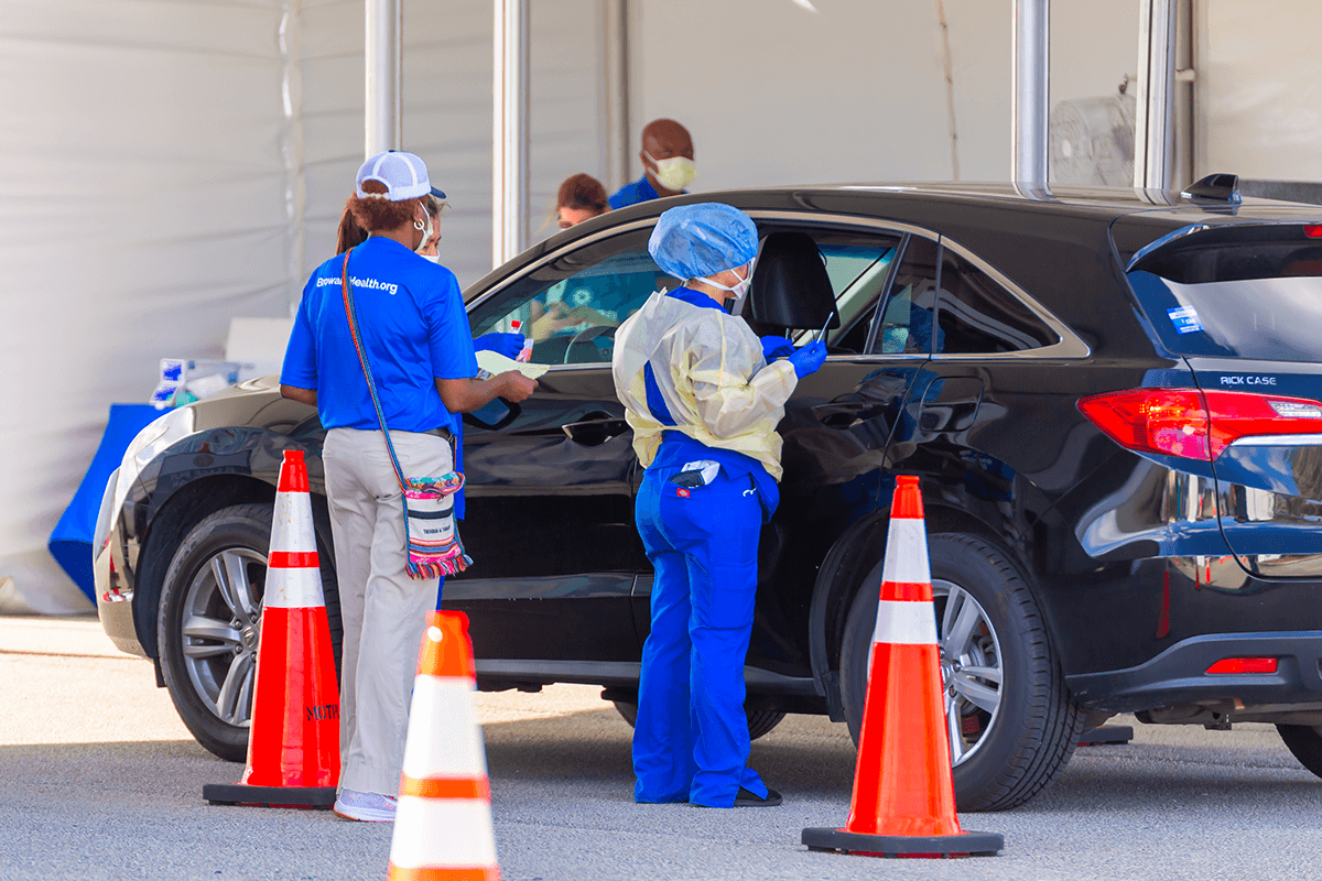 Healthcare workers collect COVID-19 samples at a drive-through testing site in Florida.