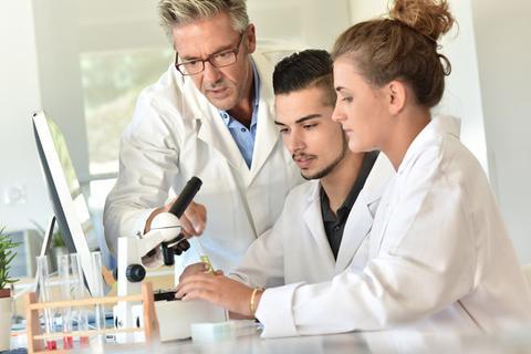 Three scientists around a microscope