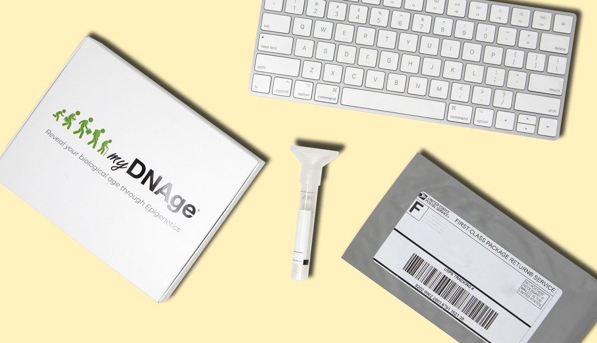 Image of a keyboard, a booklet of myDNAge, a mailing envelope, and the SafeCollect Saliva Test Collection Kit